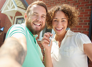 Couple taking selfie and holding up keys in front of new house.