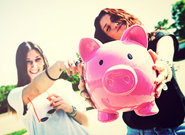 Young ladies holding out piggy bank.