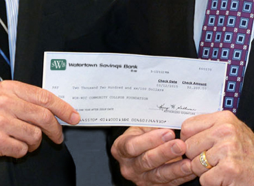 Photo of a close up of a Watertown Savings Bank check being presented to an individual as a donation.