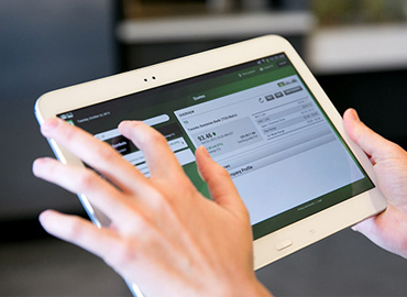 a person holding a tablet using it for their online banking